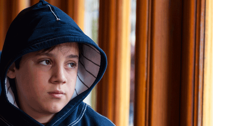 Young boy appearing sad and standing indoors.