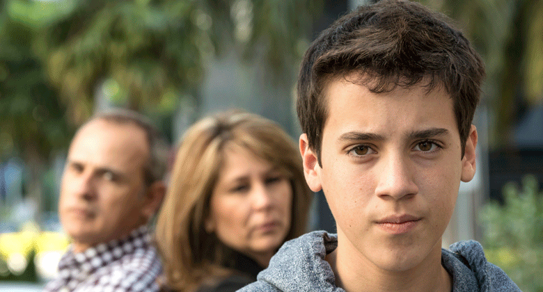 Teen boy standing outdoors with parents