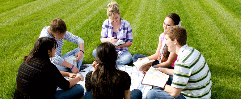 Teenagers outside studying bible.