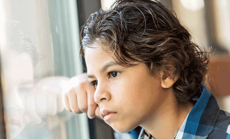 Young boy staring out the window.