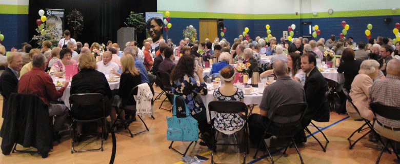 Dinner attendees sitting at tables in Crossroad gym event