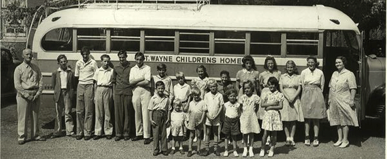 Historic photo of St. Wayne Children's Home students gathered in front of old school bus