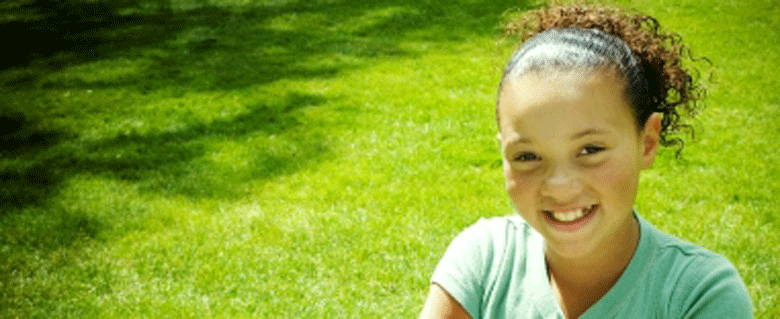 Young girl sitting on grass looking upwards to camera